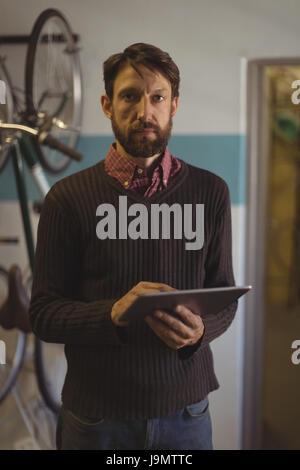 Portrait de l'employé à l'aide de tablette numérique à l'atelier de vélo Banque D'Images