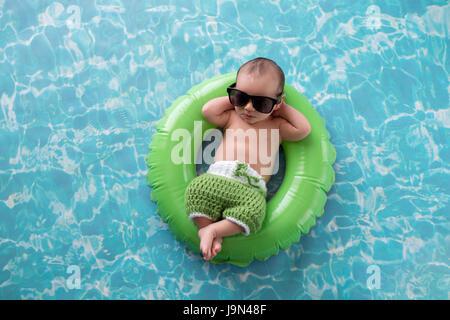 Deux semaines de bébé nouveau-né garçon endormi sur une toute petite, verte, anneau de bain gonflable. Il porte Banque D'Images