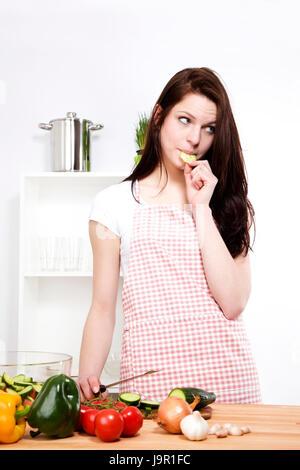 Jeune femme grignoter un concombre Banque D'Images