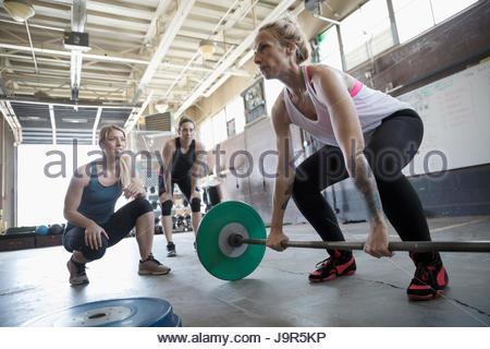 La motivation des femmes ami haltérophilie, faisant au deadlift Haltères fitness graveleux Banque D'Images