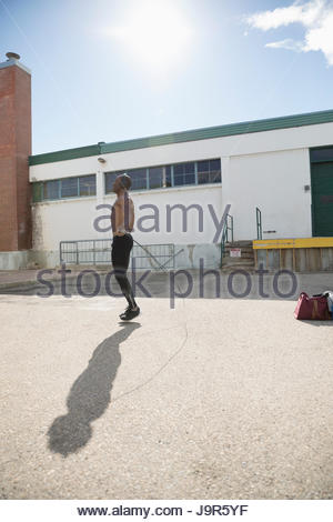 Torse nu fit man jumping rope en stationnement ensoleillée Banque D'Images