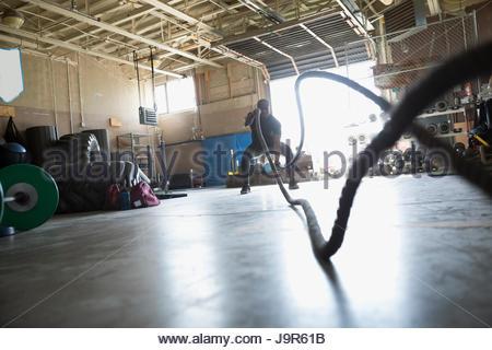 L'homme faisant combattre crossfit gym dans l'exercice de cordes Banque D'Images