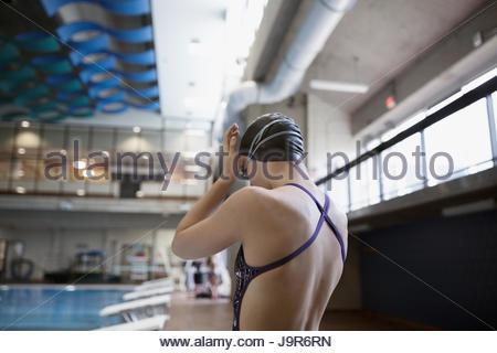 Teenage girl swimmer préparer lunettes de natation à la piscine Banque D'Images