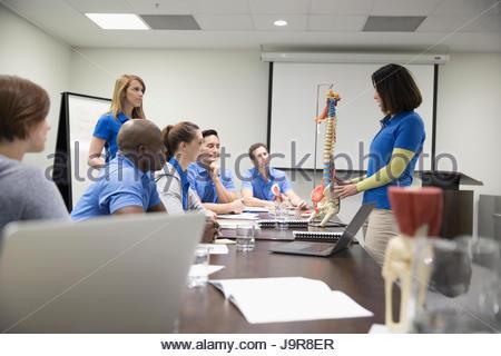 Les physiothérapeutes avec spine model formation au coffre dans la salle de conférence réunion Banque D'Images