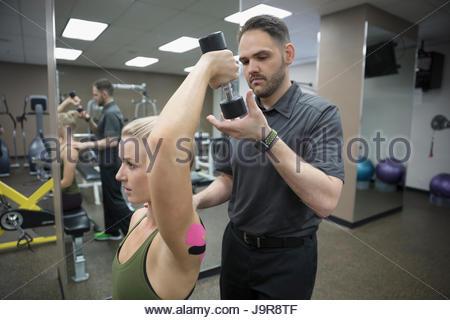 Physiothérapeute mâle femelle aidant à s'entraîner avec le client en haltère fitness clinique Banque D'Images