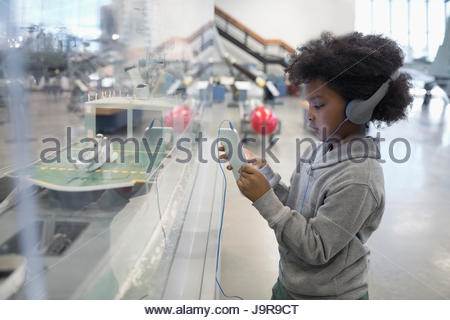 Curieux African boy student wearing headphones using digital tablet et exposition sur le terrain dans la guerre Banque D'Images