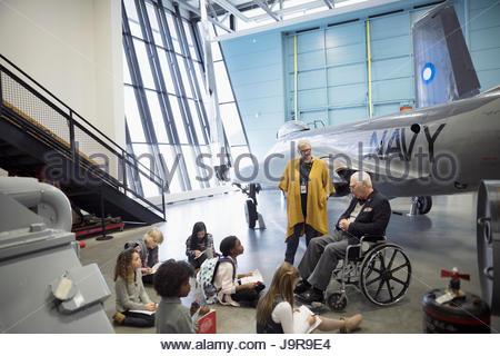 Docent et ancien combattant, de parler aux étudiants sur l'excursion au musée de la guerre navale en avion hangar Banque D'Images
