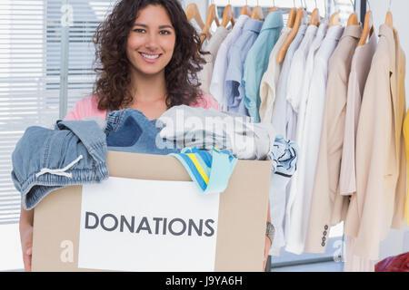 Jolie boîte de dons bénévoles holding clothes