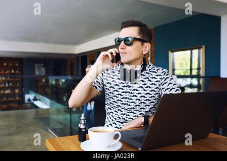 Beau jeune homme hipster dans sunglases assis dans cafe parle téléphone mobile. Ordinateur portable sur une table Banque D'Images