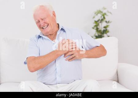 Un homme avec la douleur cardiaque sur un canapé Banque D'Images