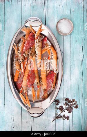 Assiette ovale avec des matières les homards et rascasses sur fond de bois, avec le gros sel et le thym fleurs, Banque D'Images