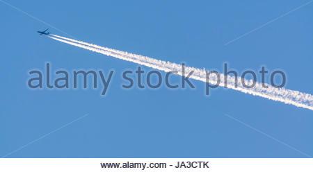Les traînées de condensation d'un avion à réaction de haut vol dans le ciel contre ciel bleu. Banque D'Images