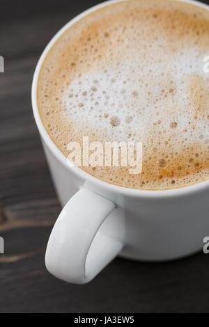 Close-up d'une tasse de Cappuccino blanc sur un tableau noir en bois. Un plan macro. Banque D'Images