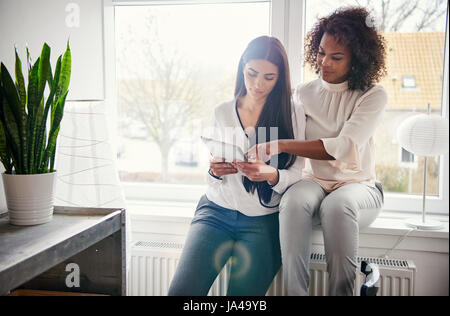 Deux jeunes femmes travaillant sur un ordinateur tablette, assis ensemble sur un rebord lumineux dans le bureau Banque D'Images