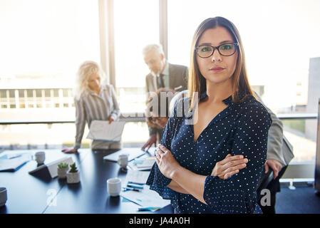 Femme d'affaires graves devant team, looking at camera Banque D'Images