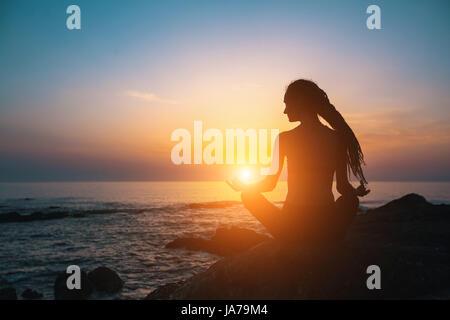 Fille de méditation sur la mer au coucher du soleil. Silhouette de yoga. Condition physique et mode de vie sain.