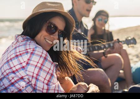 Groupe d'amis avec la guitare sur la plage partie Banque D'Images