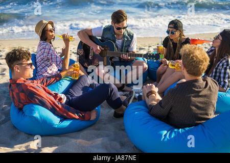 Groupe d'amis avec de la guitare et de l'alcool sur la plage partie Banque D'Images