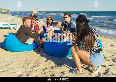 Fille prend une photo de groupe d'amis sur la plage Banque D'Images