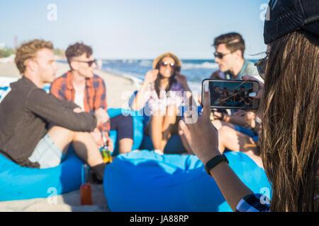 Vue rapprochée de la fille prend une photo de groupe d'amis sur la plage Banque D'Images