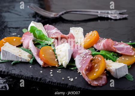 Salade avec du jambon jamon serrano, camembert, roquette, melon sur plaque ardoise noire sur fond noir. Close up. Banque D'Images