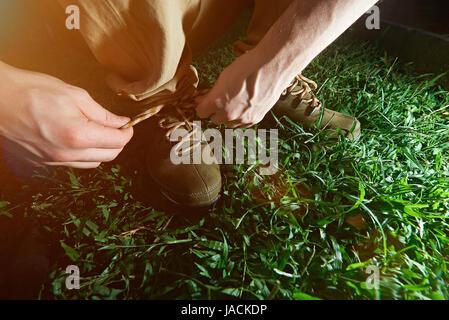 Lier l'homme sur ses lacets de chaussures active libre fond d'herbe verte