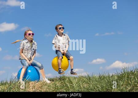 Frère et sœur jouant sur le terrain à la journée. Les enfants s'amuser en plein air. Ils sauter sur des ballons Banque D'Images