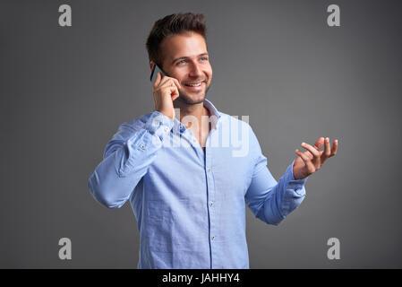 Un beau jeune homme souriant tout en parlant sur un smartphone Banque D'Images