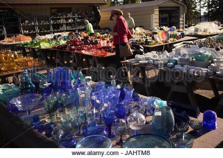 Consommateurs à la recherche de verres colorés à un marché aux puces. Banque D'Images