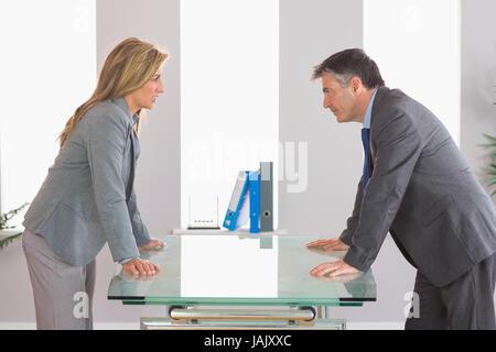 Deux irrités businesspeople standing arguant de chaque côté d'un bureau à l'office de tourisme Banque D'Images