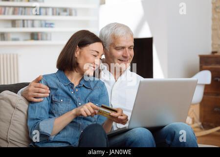 Mature Couple connecté avec un ordinateur portable et des achats en ligne Banque D'Images