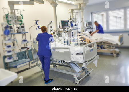 Nurse with patient sur l'unité de soins intensif