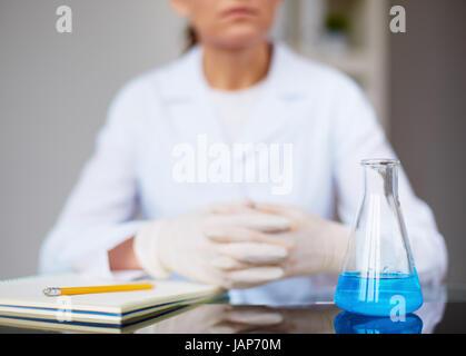 Image de flacon en verre avec un liquide bleu et femelle chimiste dans l'arrière-plan Banque D'Images