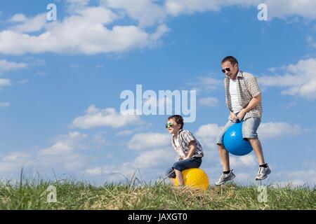 Père et fils jouant sur le terrain à la journée. Les gens s'amuser à l'extérieur. Ils sauter sur des ballons gonflables Banque D'Images