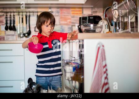 Enfant d'âge préscolaire, garçon, aider maman, mettre la vaisselle sale dans le lave-vaisselle à la maison, cuisine Banque D'Images