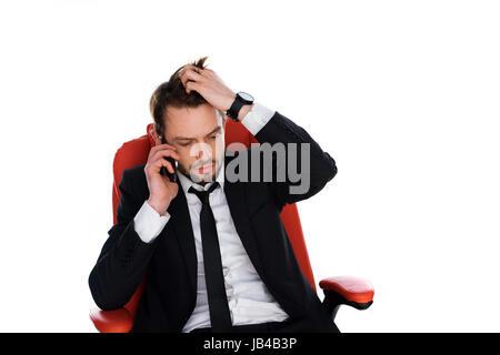 De peur d'une chaise de bureau rouge sur son téléphone mobile et passer ses mains dans ses cheveux dans l'anxiété, Banque D'Images