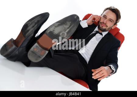 Businessman relaxing satisfait avec succès dans son bureau, se penchant avec contentement adossé sur sa chaise avec Banque D'Images