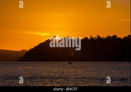Coucher du soleil doré disparaître derrière la terre en mer océan dans Plymouth, Devon, England, UK Banque D'Images