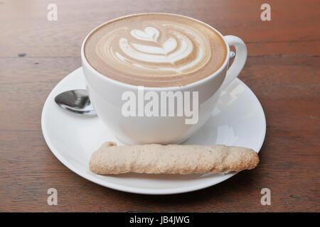 Latte art café avec motif coeur dans une tasse blanche et des cookies sur fond de bois Banque D'Images