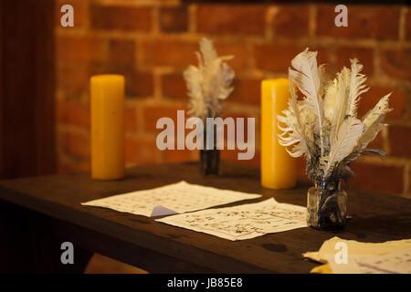 Plumes plumes bougie et vieux papiers sur un bureau en bois