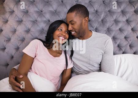 Smiling couple embracing while sitting on bed at home Banque D'Images