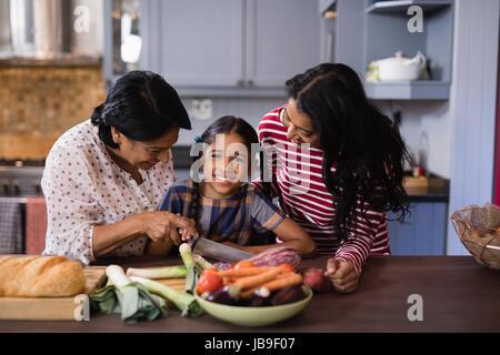 Portrait de jeune fille de préparer les aliments avec la mère et grand-mère dans la cuisine à la maison Banque D'Images