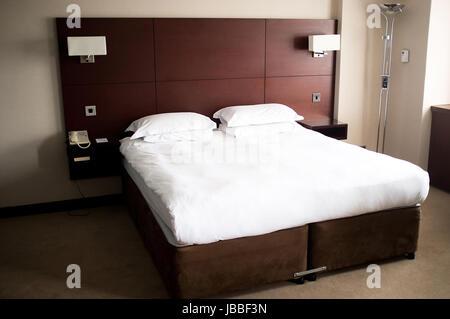 Grand lit dans une suite avec des feuilles blanches sur elle et une tête Banque D'Images