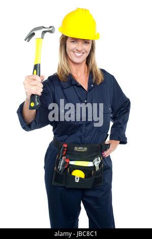 Construction Worker holding en uniforme jusqu'à inertie avec tool kit autour de sa taille. Banque D'Images