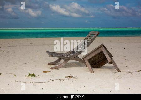Table brisée et siège en bois, sur une plage déserte dans les Maldives. Banque D'Images