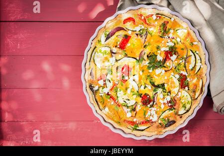 Des petits salés quiche aux aubergines, poivrons, tomates et fromage assaisonné de fines herbes dans un plat à tarte Banque D'Images