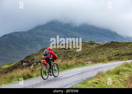 Lonely biker vélo dans les Highlands écossais, lourdement chargé sur vélos de cyclotourisme le long de la route Banque D'Images