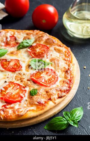 Pizza Margherita sur fond noir en noir. Des pizzas Margarita avec tomates, basilic et mozzarella. Banque D'Images