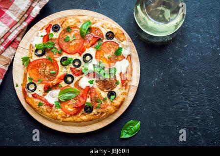Pizza italienne avec tomates, olives noires, de salami et de fromage Mozzarella, vue du dessus. Des pizzas fraîches. Banque D'Images