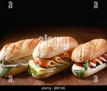 Trio composé de baguettes végétariennes d'or avec une variété de garnitures de fromage aux herbes et ingrédients Banque D'Images